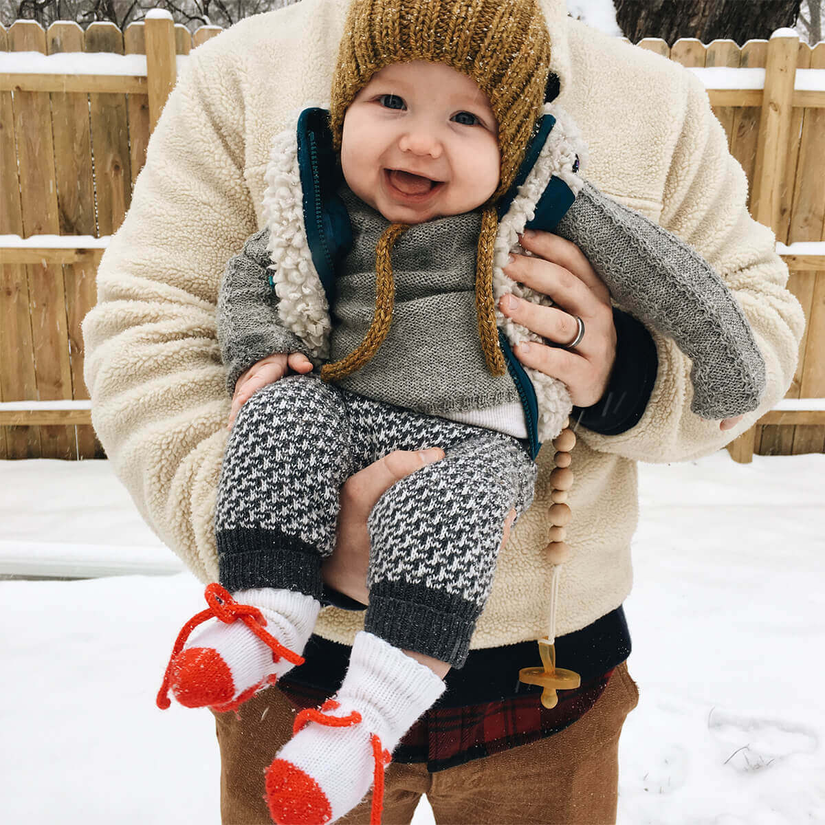 Baby in beanie outside laughing in dad's arms