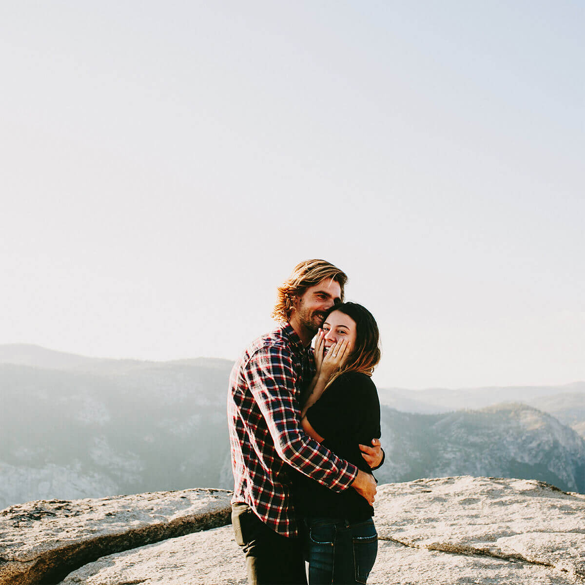 Couple embracing on top of mountain after engagement proposal