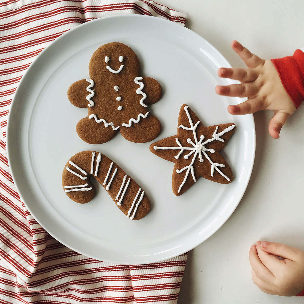 Child's hand grabbing cookie from plate