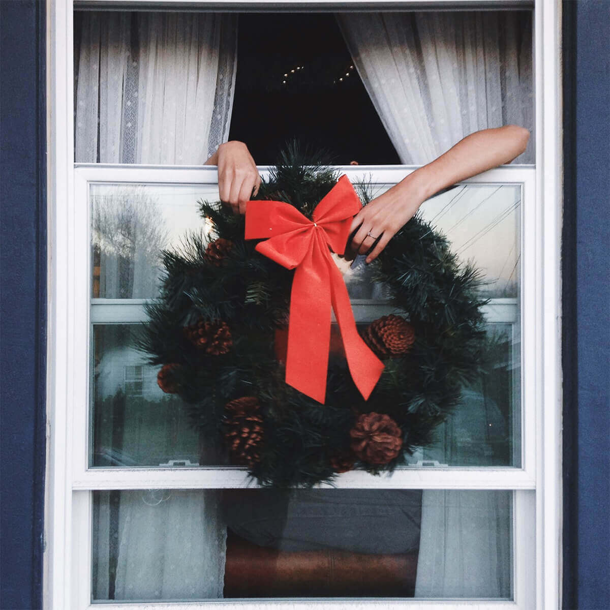 Hands holding a wreath out the window