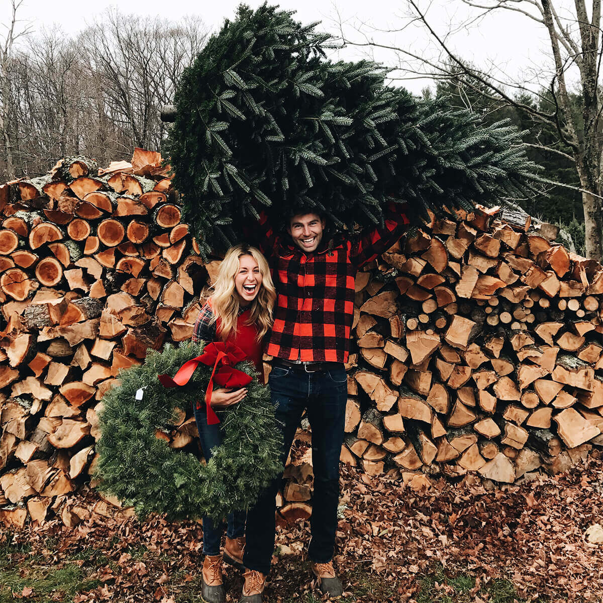 Couple holding wreath and freshly cut pine tree in front of large stack of logs