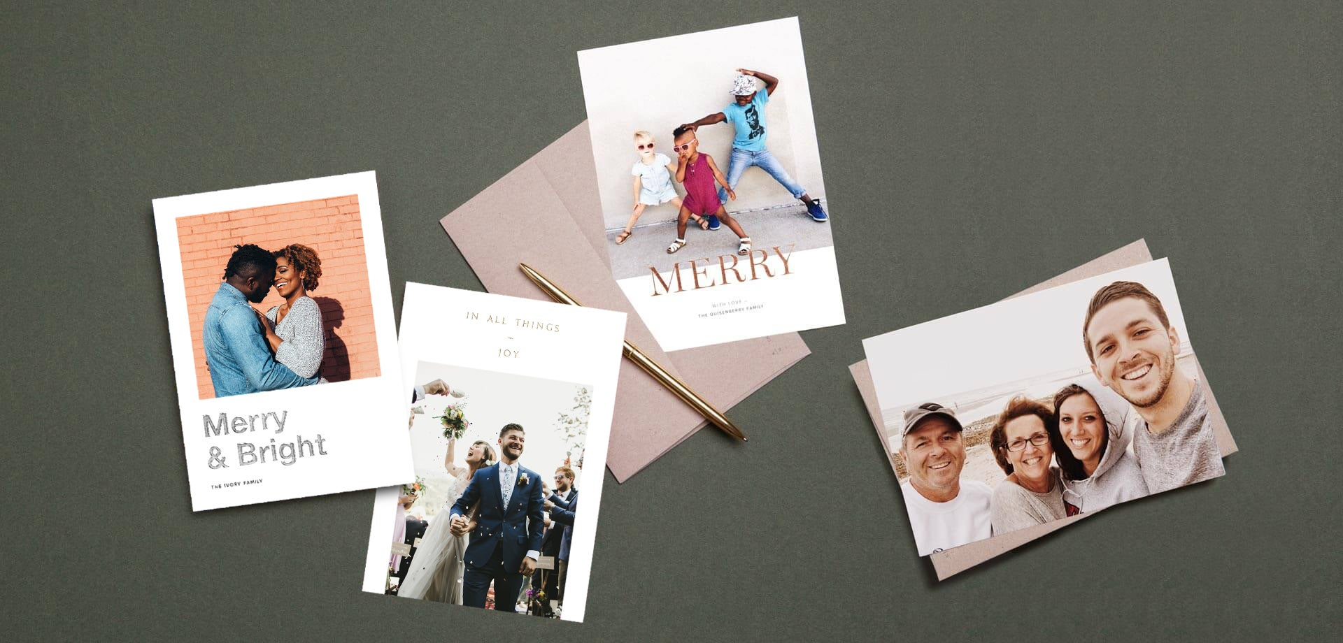 holiday cards spread out on table with gold pen