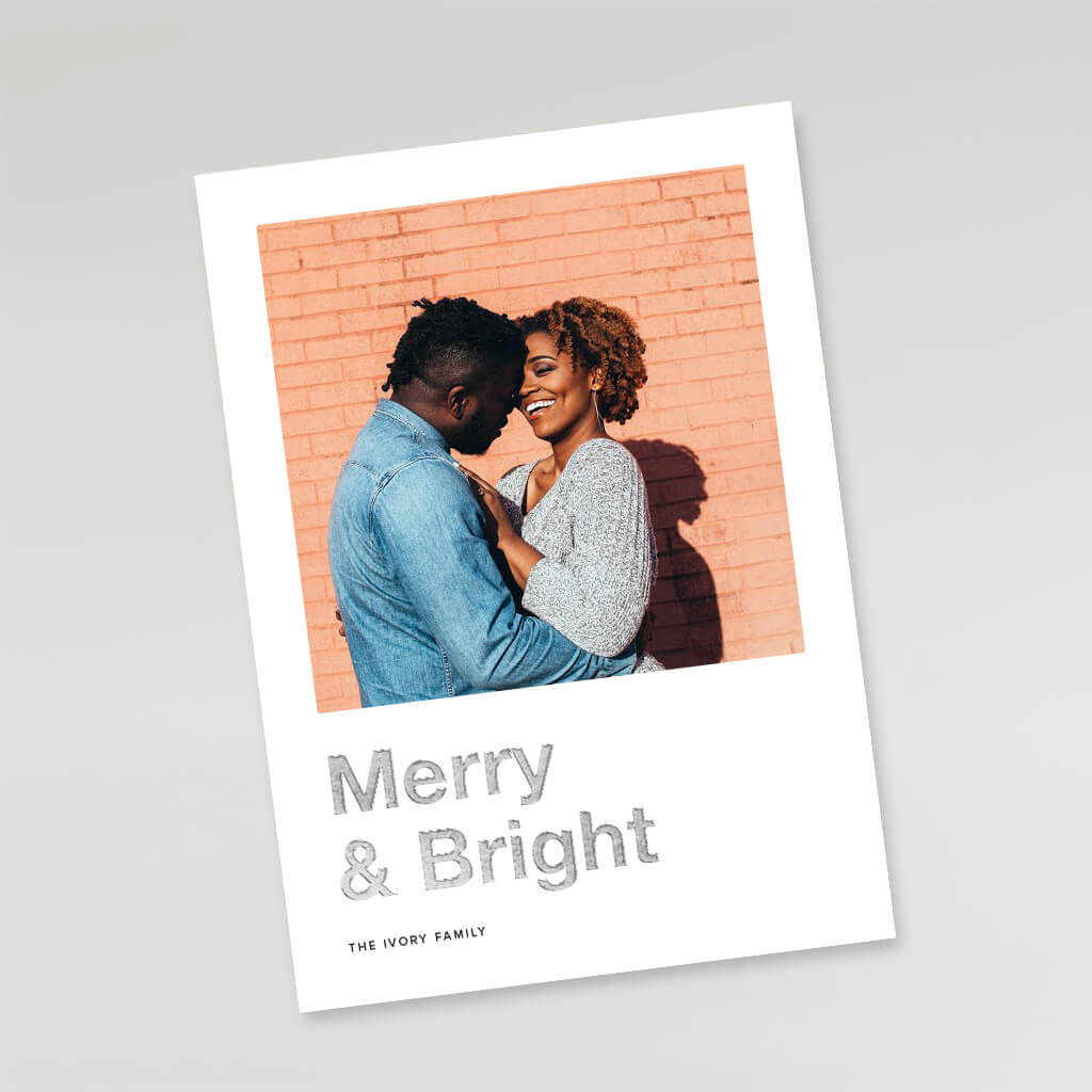 couple kissing in front of brick wall on holiday card
