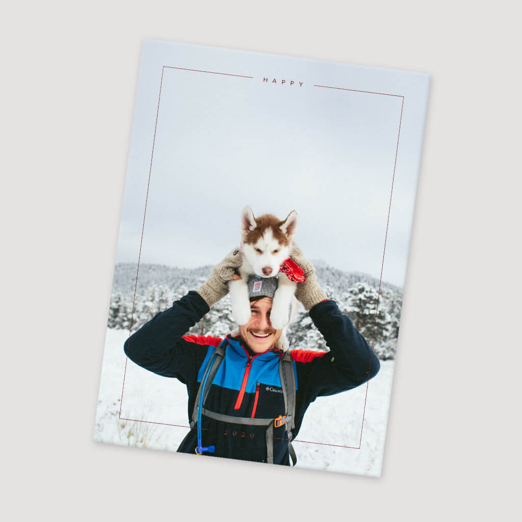 man in the outdoors holding husky above his head in winter scene