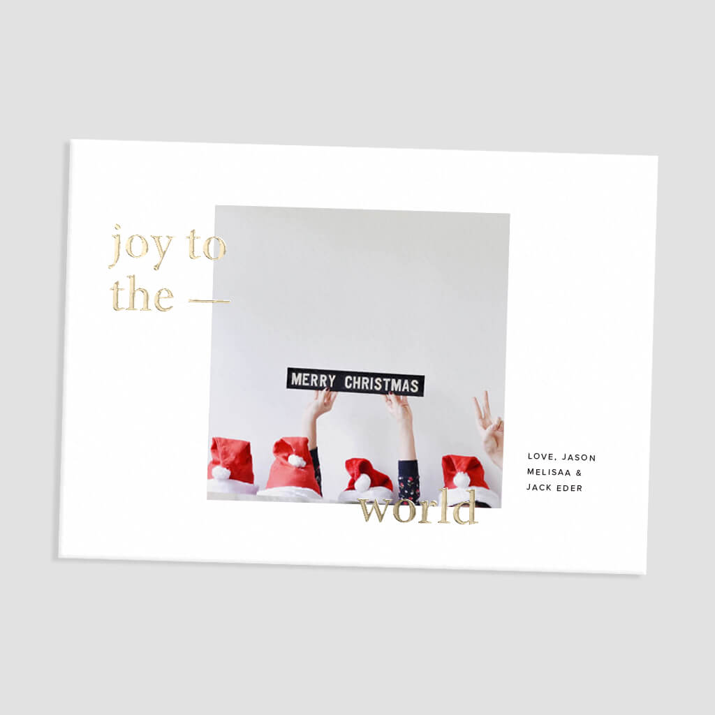 Holiday card with photo of tops of Santa hats and hands holding up Merry Christmas decal