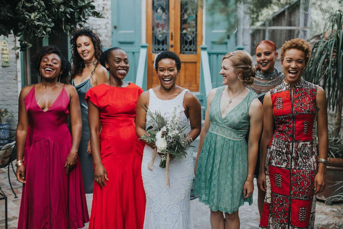 Bridesmaids in vibrant mismatched dresses standing next to bride outside of venue