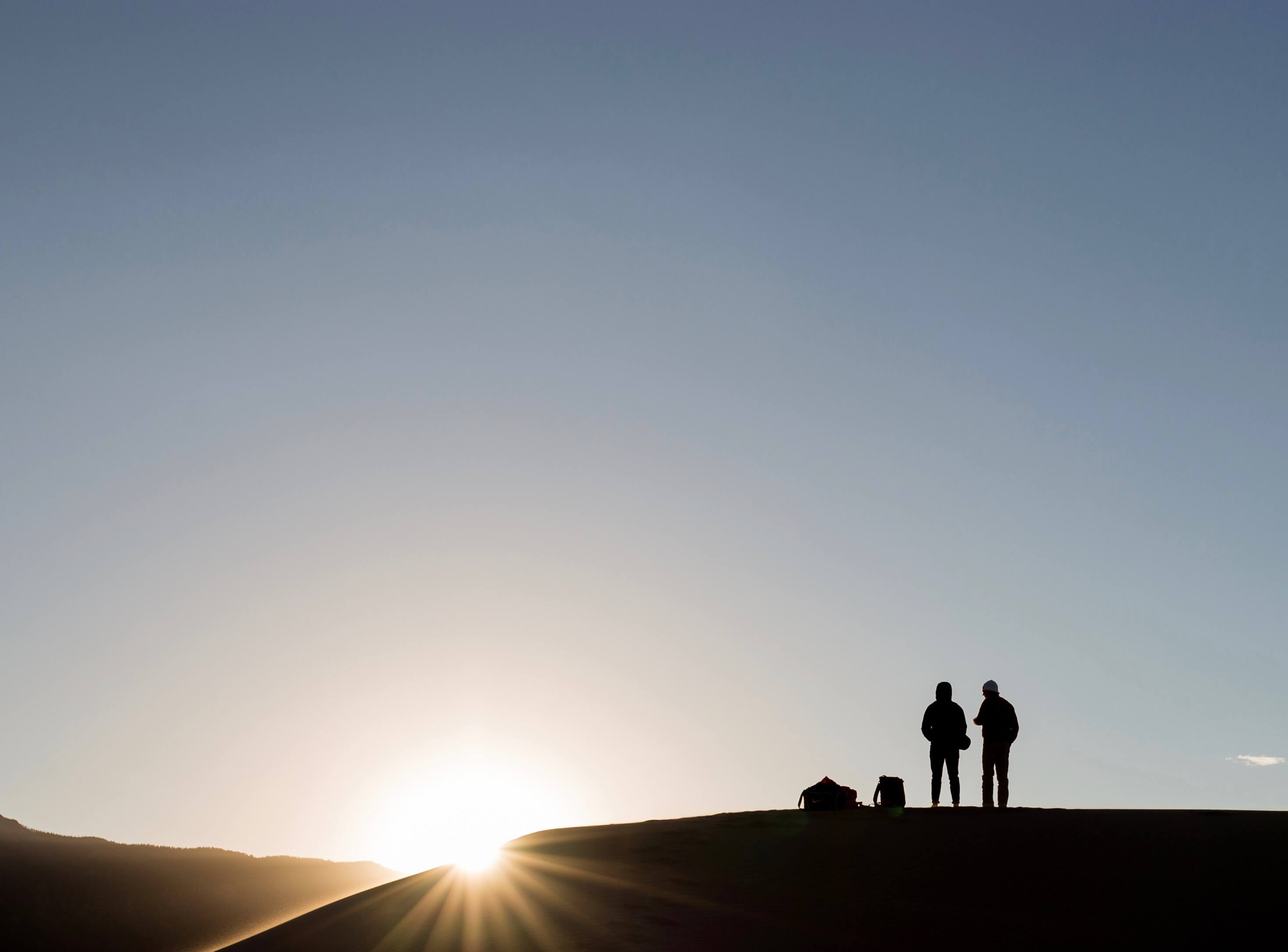 Silhouette of a couple atop a sand dune at sunset
