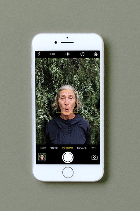 iPhone screen taking photo of elderly woman in portrait mode