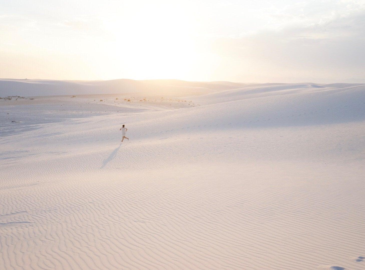Woman running across the desert sand at dusk