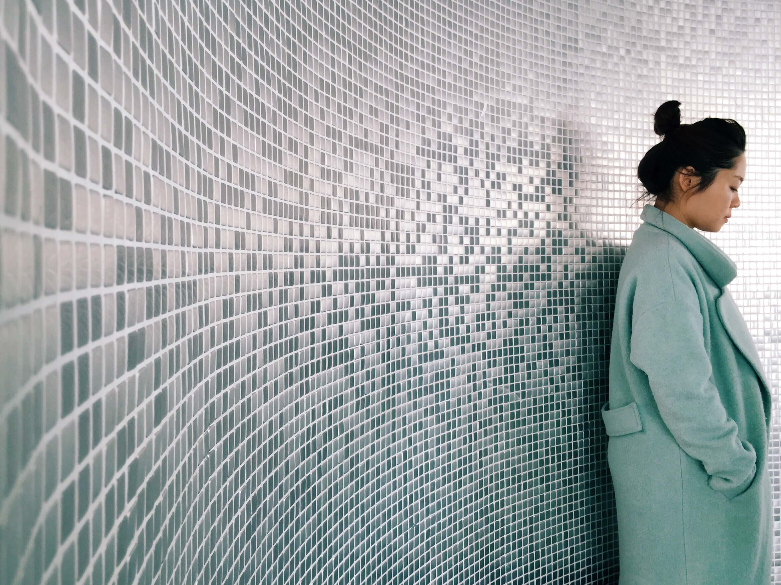 woman leaning against textured wall