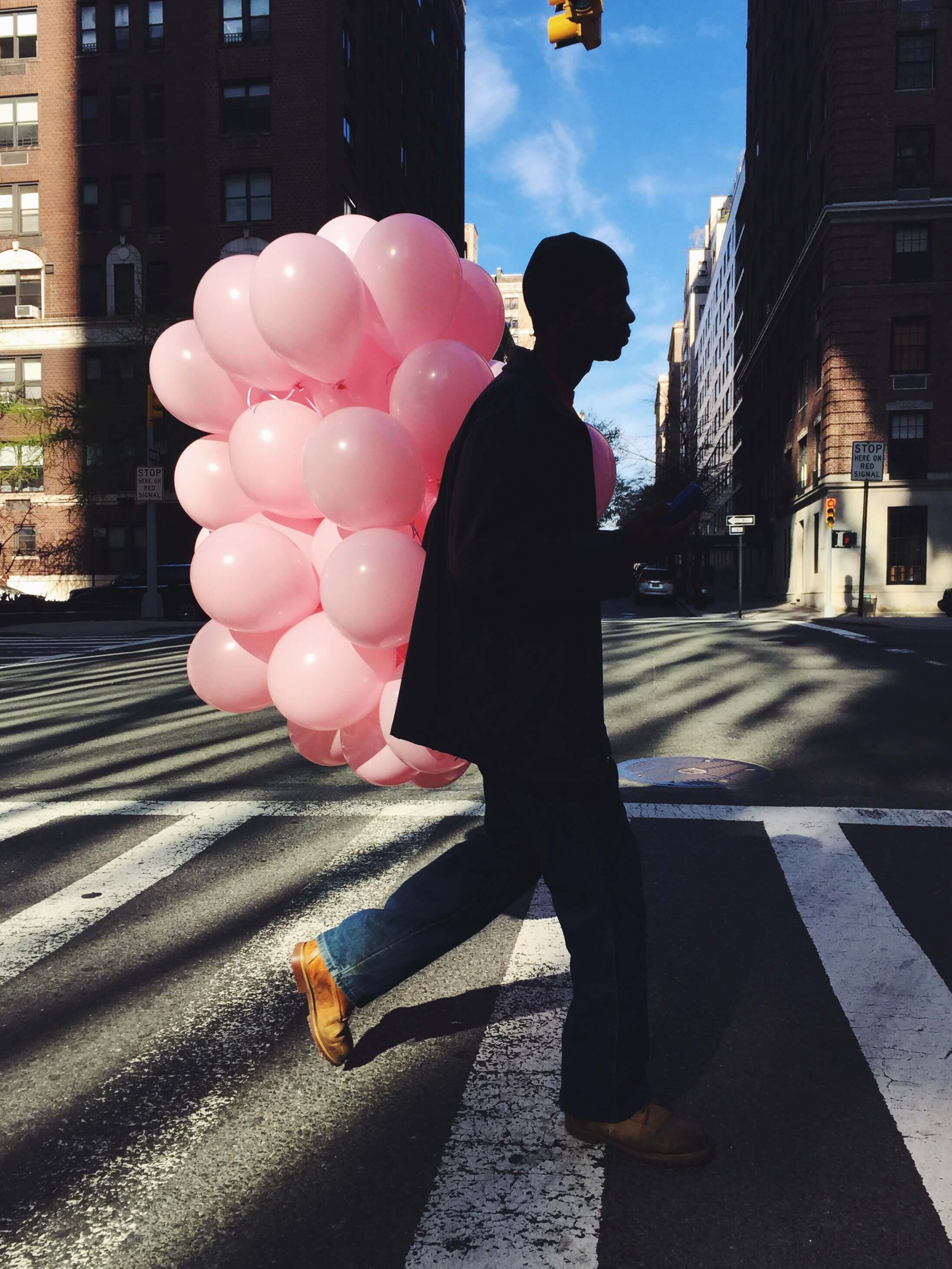 silhouette of a man carrying many pink balloons