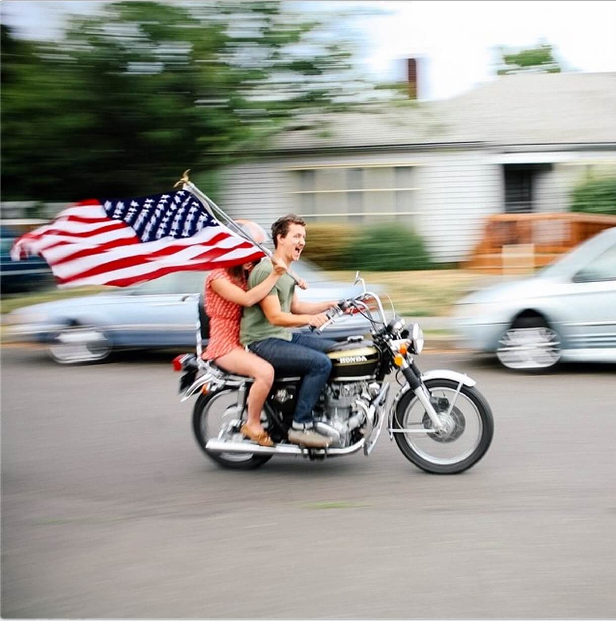 Motion blur photo of couple riding motorcycle holding USA flag