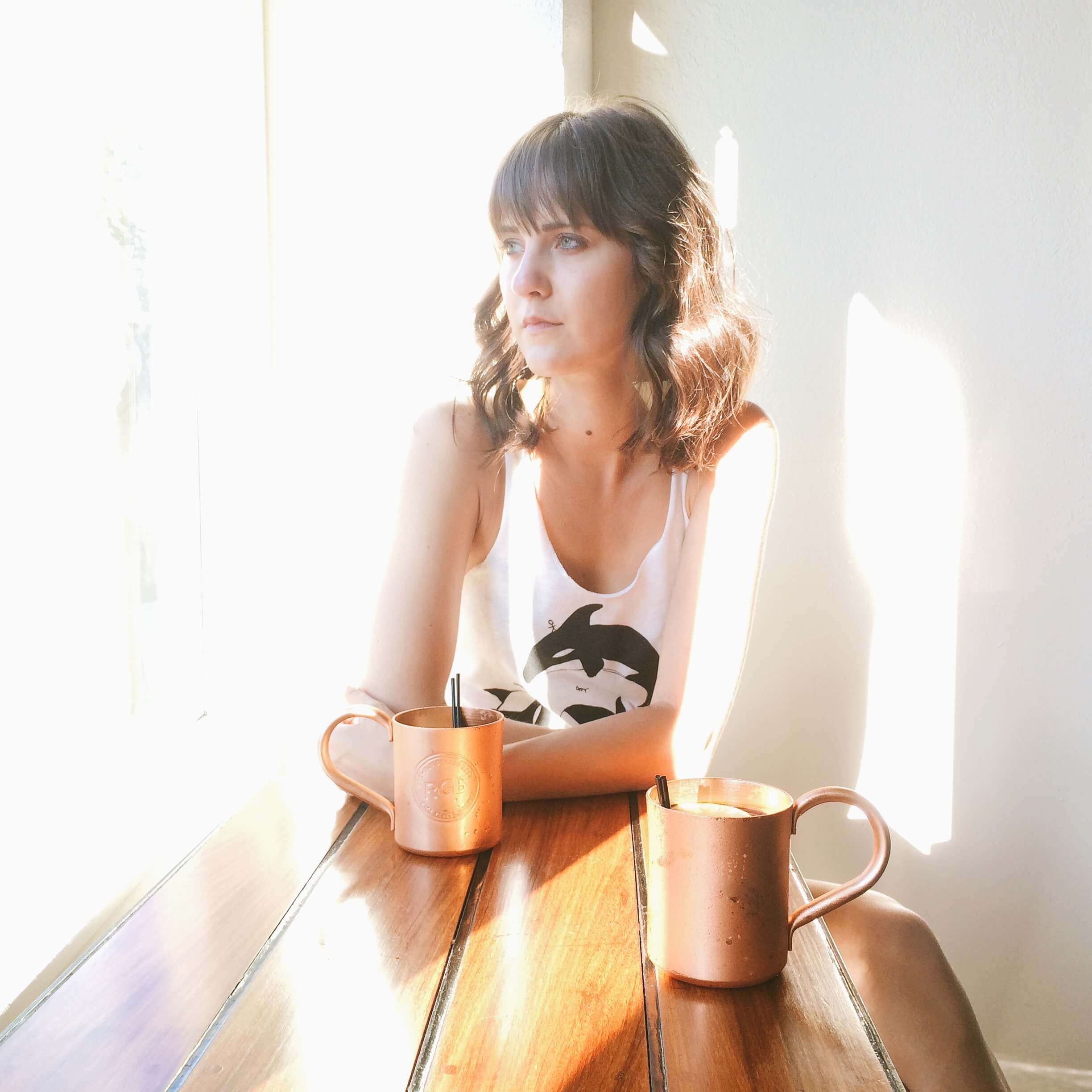 Photo of woman shrouded in light drinking Moscow Mule next to a window