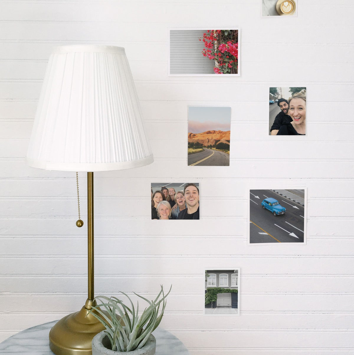 Prints on white brick wall next to lamp